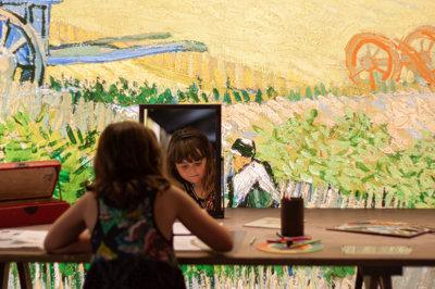 Een meisje tekent in de Experience haar eigen zelfportret met behulp van een spiegel.
