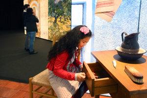 Een meisje maakt een lade open in de Meet Vincent Van Gogh Experience