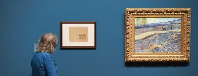 In de tentoonstelling vergelijkt een vrouw de briefschets van Vincent van Gogh met het het schilderij Veld met een ploeger uit 1889. Foto: Tomek Dersu Aaron