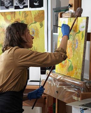 Charlotte Caspers werkt aan haar kleurenreconstructie van de 'Zonnebloemen'.