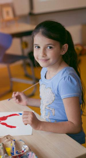 Een meisje met blauw t-shirt en penseel in de hand kijkt lachend naar de camera. Op de tafel voor haar ligt haar schilderij. Foto: Brenda Roos